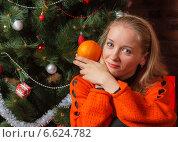 Девушка в красном свитере с апельсином возле новогодней елки. Стоковое фото, фотограф Ольга Хорькова / Фотобанк Лори