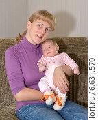 Купить «Молодая женщина сидит на диване с грудным ребенком на руках», фото № 6631570, снято 12 октября 2014 г. (c) Ирина Борсученко / Фотобанк Лори