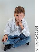 Мальчика в белой рубашке и синих джинсах сидит. Стоковое фото, фотограф Сергей Богданов / Фотобанк Лори