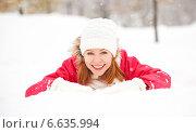 Счастливая девушка лежит в снегу в зимнем парке. Стоковое фото, фотограф Евгений Атаманенко / Фотобанк Лори