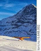 Маленький желтый самолет садится на снег в швейцарских Альпах (2013 год). Стоковое фото, фотограф Роман Бабакин / Фотобанк Лори