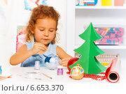 Купить «Девочка расписывает елочный шарик», фото № 6653370, снято 26 октября 2014 г. (c) Сергей Новиков / Фотобанк Лори