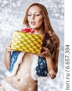 Молодая сексуальная женщина сдувает снег с новогоднего подарка. Стоковое фото, фотограф katalinks / Фотобанк Лори