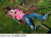 Купить «Девочка лежит в садовой тачке», фото № 6668254, снято 21 сентября 2014 г. (c) Денис Шароватов / Фотобанк Лори