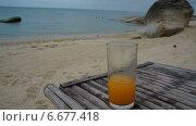 Опустошение бокала сока,  стоящего на деревянном столе на пляже. Стоковое видео, видеограф Леван Каджая / Фотобанк Лори