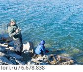 Купить «Отец с сыном ловят форель в озере. Взрослый поймал рыбу и заводит ее в сачок, который держит ребенок», фото № 6678838, снято 16 ноября 2014 г. (c) Ирина Кожемякина / Фотобанк Лори