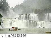 Купить «Туристы на бамбуковом плоту плывут близко к водопаду Ban Gioc или Detian на границе между Вьетнамом и Китаем», фото № 6683946, снято 15 августа 2014 г. (c) Жукова Юлия / Фотобанк Лори