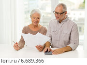 senior couple with papers and calculator at home. Стоковое фото, фотограф Syda Productions / Фотобанк Лори