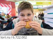 Купить «Мальчик ест гамбургер в кафе», фото № 6722002, снято 3 ноября 2014 г. (c) Володина Ольга / Фотобанк Лори