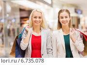 Купить «happy young women with shopping bags in mall», фото № 6735078, снято 3 ноября 2014 г. (c) Syda Productions / Фотобанк Лори
