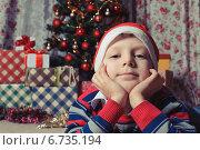 Мечтательный мальчик на фоне новогодней елки с подарками. Стоковое фото, фотограф Сергей Богданов / Фотобанк Лори