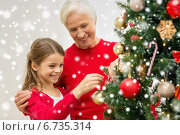 Купить «smiling family decorating christmas tree at home», фото № 6735314, снято 14 сентября 2014 г. (c) Syda Productions / Фотобанк Лори