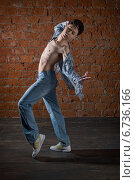 Молодой азиатский мужчина в джинсах и рубашке танцует на фоне кирпичной стены. Стоковое фото, фотограф Okssi / Фотобанк Лори