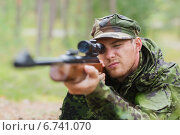 Купить «young soldier or hunter with gun in forest», фото № 6741070, снято 14 августа 2014 г. (c) Syda Productions / Фотобанк Лори