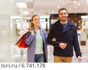Купить «happy young couple with shopping bags in mall», фото № 6741178, снято 10 ноября 2014 г. (c) Syda Productions / Фотобанк Лори