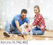 Купить «smiling couple measuring wood flooring», фото № 6742402, снято 26 января 2014 г. (c) Syda Productions / Фотобанк Лори
