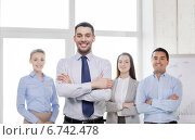 Купить «smiling businessman in office with team on back», фото № 6742478, снято 5 апреля 2014 г. (c) Syda Productions / Фотобанк Лори