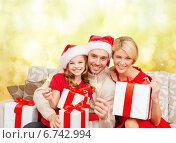 Купить «smiling family holding gift boxes and sparkles», фото № 6742994, снято 26 октября 2013 г. (c) Syda Productions / Фотобанк Лори