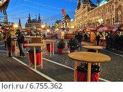 Купить «Деревянные столики уличного кафе и торговые палатки. ГУМ-ярмарка на Красной площади в Москве вечером», эксклюзивное фото № 6755362, снято 3 декабря 2014 г. (c) lana1501 / Фотобанк Лори