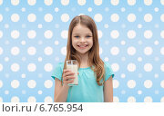 Купить «smiling girl with glass of milk over polka dots», фото № 6765954, снято 9 апреля 2014 г. (c) Syda Productions / Фотобанк Лори