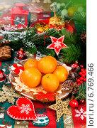 Купить «Новогодний стол с мандаринами и елочными украшениями», фото № 6769466, снято 21 декабря 2013 г. (c) ElenArt / Фотобанк Лори
