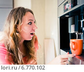 Купить «Удивленная женщина смотрит на кофемашину на кухне», фото № 6770102, снято 18 сентября 2013 г. (c) Валерия Потапова / Фотобанк Лори