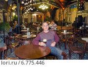 Купить «Мужчина пьет кофе в кафе города Львова, Украина», фото № 6775446, снято 4 ноября 2014 г. (c) Несинов Олег / Фотобанк Лори