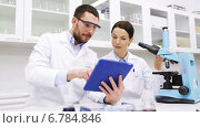 Купить «scientists with tablet pc and microscope in lab», видеоролик № 6784846, снято 7 декабря 2014 г. (c) Syda Productions / Фотобанк Лори