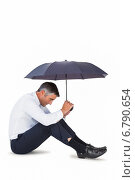 Купить «Businessman sitting and sheltering with umbrella», фото № 6790654, снято 12 июня 2014 г. (c) Wavebreak Media / Фотобанк Лори