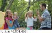 Счастливая семья с двумя детьми проводит время на природе, девочка играет в ладошки с папой. Стоковое видео, видеограф Denis Mishchenko / Фотобанк Лори