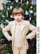 Купить «Капризный возмущенный мальчик в бежевом костюме на фоне новогодней елки», фото № 6806266, снято 13 декабря 2014 г. (c) Юлия Кузнецова / Фотобанк Лори