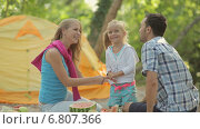 Симпатичная маленькая  девочка с родителями на открытом воздухе с арбузом. Стоковое видео, видеограф Denis Mishchenko / Фотобанк Лори