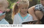 Купить «Красивая девочка сидит с планшетом в окружении своей семьи на природе», видеоролик № 6807514, снято 12 декабря 2014 г. (c) Denis Mishchenko / Фотобанк Лори