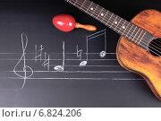 Купить «Гитара и маракасы на доске с музыкальными нотами», фото № 6824206, снято 11 ноября 2014 г. (c) Сергей Лабутин / Фотобанк Лори