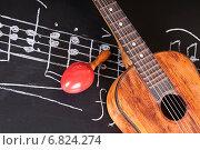 Купить «Винтажная гитара и маракасы на доске с нотами», фото № 6824274, снято 11 ноября 2014 г. (c) Сергей Лабутин / Фотобанк Лори