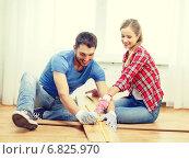 Купить «smiling couple measuring wood flooring», фото № 6825970, снято 26 января 2014 г. (c) Syda Productions / Фотобанк Лори