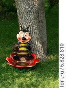 Купить «Веселая пчела с большой кружкой сидит на красном цветке. Декоративная садовая фигура - поилка», эксклюзивное фото № 6828810, снято 16 августа 2013 г. (c) Щеголева Ольга / Фотобанк Лори
