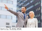 Купить «smiling businessmen standing over office building», фото № 6832854, снято 19 августа 2014 г. (c) Syda Productions / Фотобанк Лори