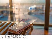 Паспорт и билет на самолёт лежат на скамейке в зале аэропорта. Стоковое фото, фотограф Константин Лабунский / Фотобанк Лори