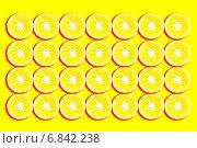 Купить «Дольки цитрусов на желтом фоне», фото № 6842238, снято 19 декабря 2010 г. (c) MMISTUDIO / Фотобанк Лори
