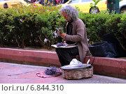Пожилая женщина на улице города продает цветы (2014 год). Редакционное фото, фотограф Сергей Лисов / Фотобанк Лори