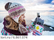 Девочка фотографирует на смартфон в около берега моря зимой. Стоковое фото, фотограф EugeneSergeev / Фотобанк Лори