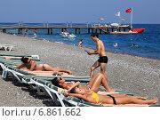 Купить «Галечный пляж в районе курортов Кемер и Чамьюва на анталийском побережье Турции, туристы загорают, лежа в шезлонгах в солнечный летний день», фото № 6861662, снято 29 августа 2014 г. (c) Владимир Григорьев / Фотобанк Лори