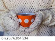 Руки в вязанных варежках держат красную кружку в белый горошек. Стоковое фото, фотограф Daodazin / Фотобанк Лори