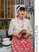 Купить «Удивлённая женщина среднего возраста стоит с буханкой хлеба на кухне», эксклюзивное фото № 6872334, снято 7 января 2015 г. (c) Игорь Низов / Фотобанк Лори