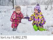 Девочки лепит снеговика. Стоковое фото, фотограф Мария Мороз / Фотобанк Лори