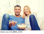 Купить «smiling couple with popcorn watching movie at home», фото № 6885370, снято 9 февраля 2014 г. (c) Syda Productions / Фотобанк Лори