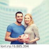 Купить «smiling couple holding big piggy bank», фото № 6885394, снято 9 февраля 2014 г. (c) Syda Productions / Фотобанк Лори
