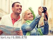 Купить «smiling couple with map and photocamera in city», фото № 6886878, снято 14 июня 2014 г. (c) Syda Productions / Фотобанк Лори
