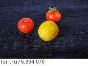 Лимон и два мандарина на черном фоне. Стоковое фото, фотограф Daodazin / Фотобанк Лори
